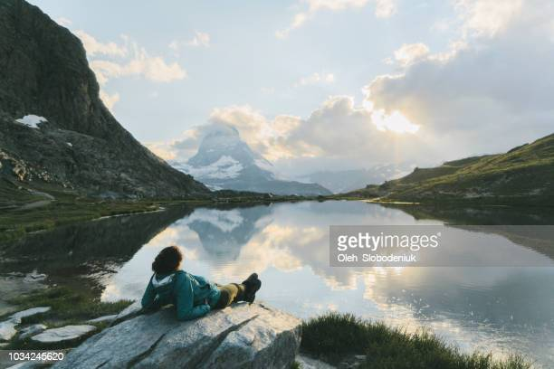 woman laying and  looking at scenic view of lake near matterhorn mountain - reflection lake stock pictures, royalty-free photos & images