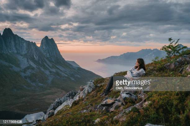 woman laying and looking at scenic view of senja - northern norway stock pictures, royalty-free photos & images