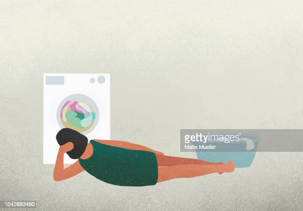 woman laying and watching clothes drying in dryer - illustration stock pictures, royalty-free photos & images
