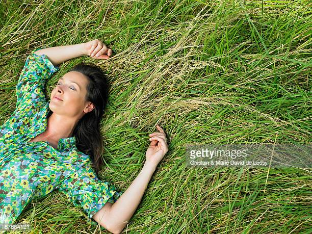 woman laying down in a field - lying down stock-fotos und bilder