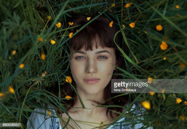 Woman laying down in green grass and yellow flowers