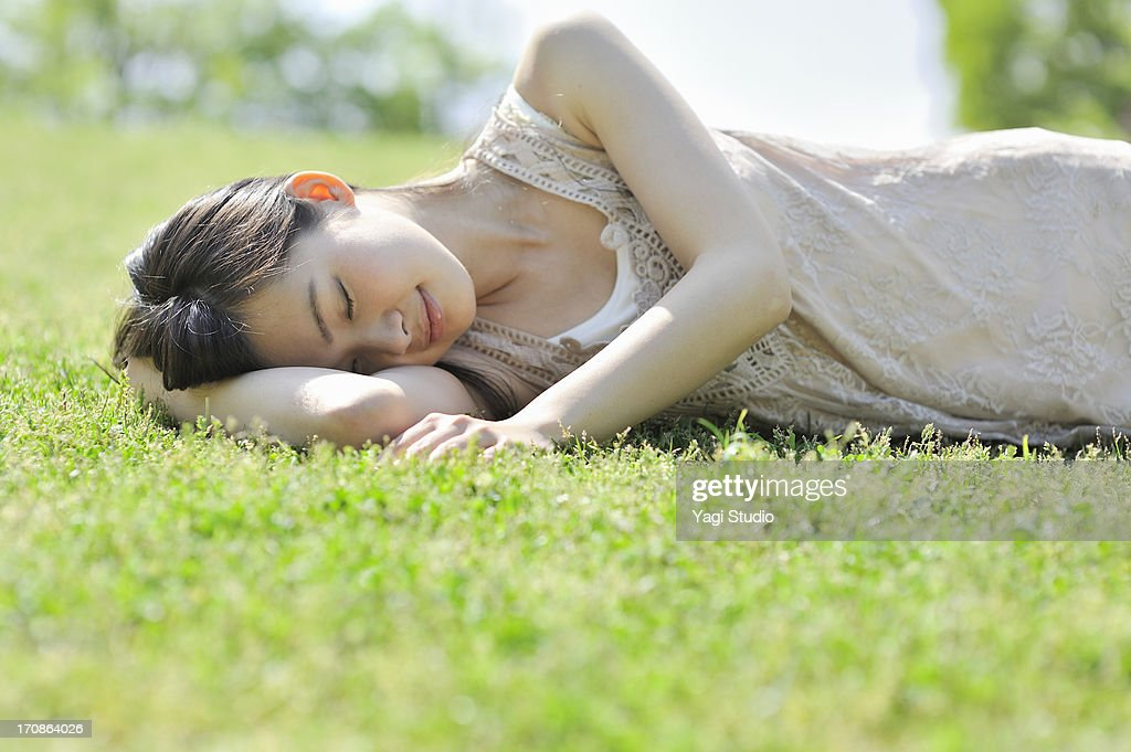 Woman laying down in nature, eyes closed : ストックフォト