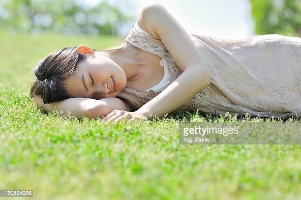 woman laying down in nature, eyes closed - lying down ストックフォトと画像