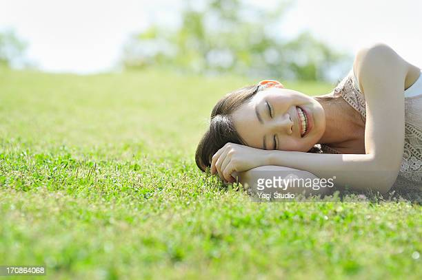 Woman laying down in nature, smiling