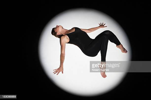Woman laying down in spotlight