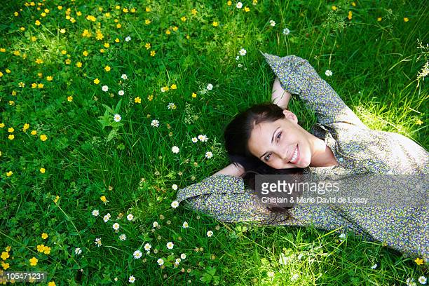 Woman laying down in the garden, smiling