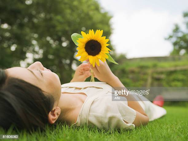 Woman Laying Down on Grass with Sunflower