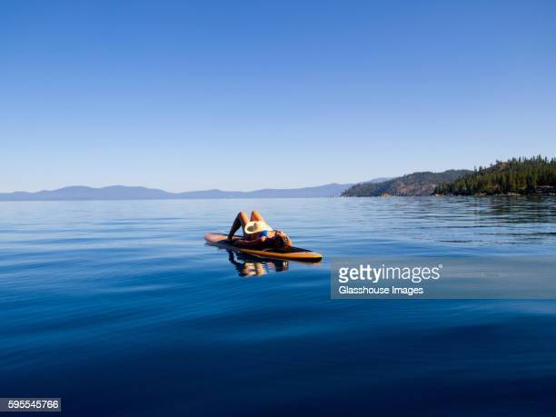 woman laying down on paddleboard on lake - nevada stock pictures, royalty-free photos & images