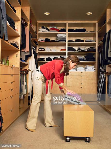 Woman laying folded clothing on bench in walk-in closet