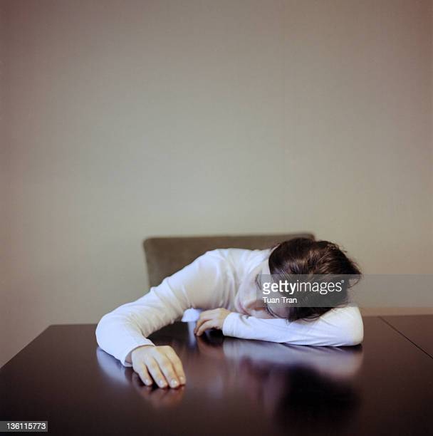 Woman laying head down on table