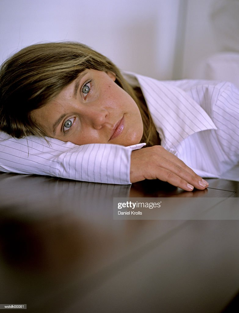 Woman laying head on table, close up : Stock Photo
