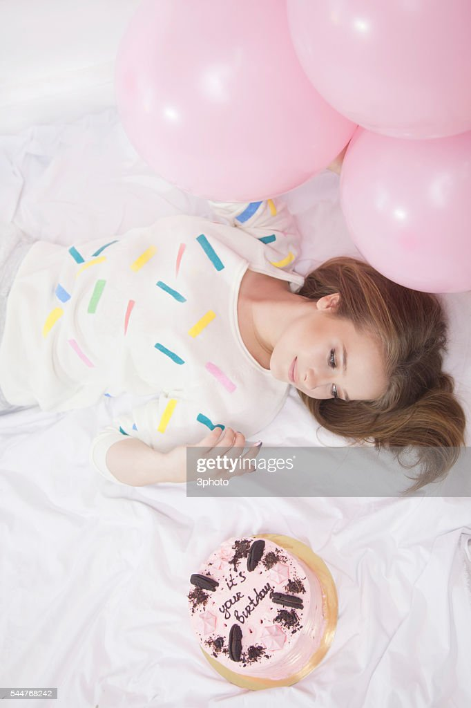 Woman Laying In Bedroom With Birthday Cake And Balloons Stock Foto