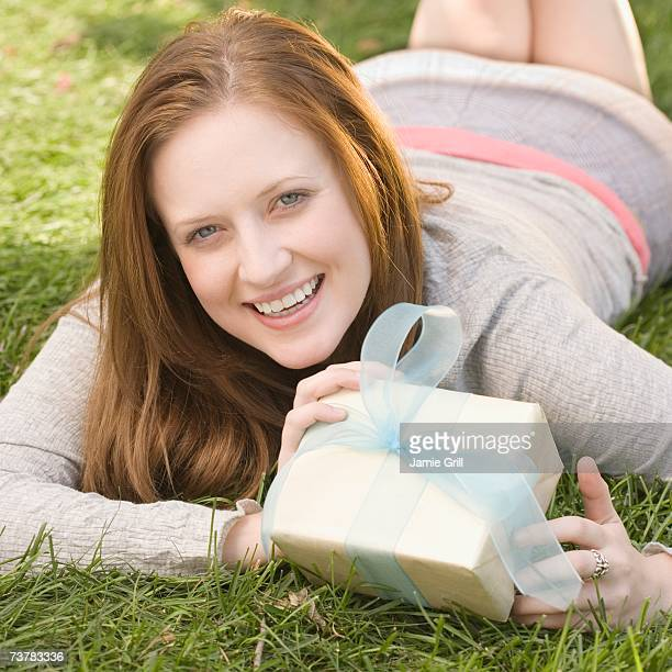 Woman laying in grass holding gift