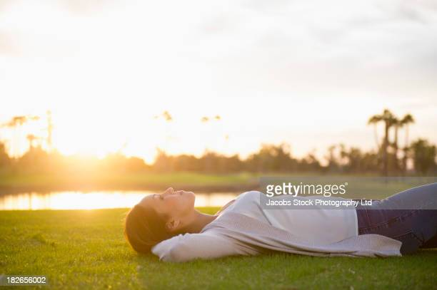 woman laying in grass - lying on back stock pictures, royalty-free photos & images
