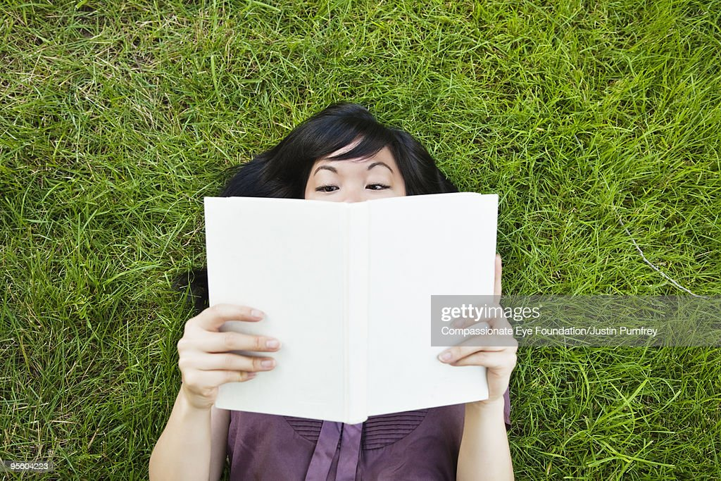 woman laying in grass reading a book : Stock Photo