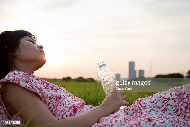 woman laying in grassy area with bottled water - health2010 ストックフォトと画像