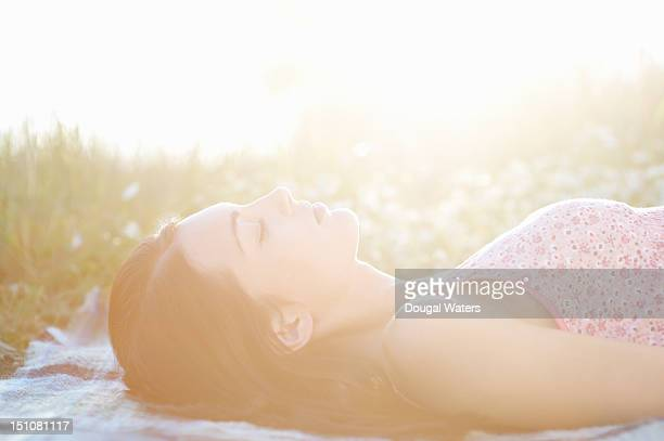 Woman laying in hazy meadow with eyes closed.