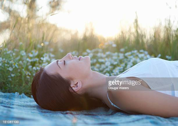 Woman laying in in meadow with eyes closed.