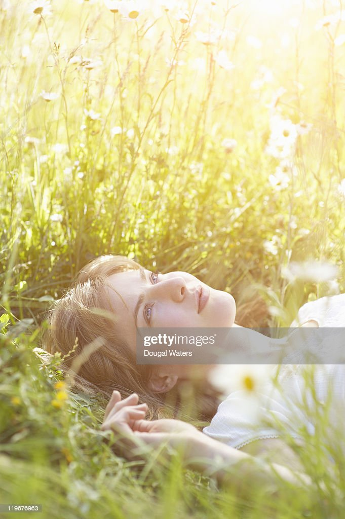 Woman laying in meadow amongst daisies. : Stock Photo