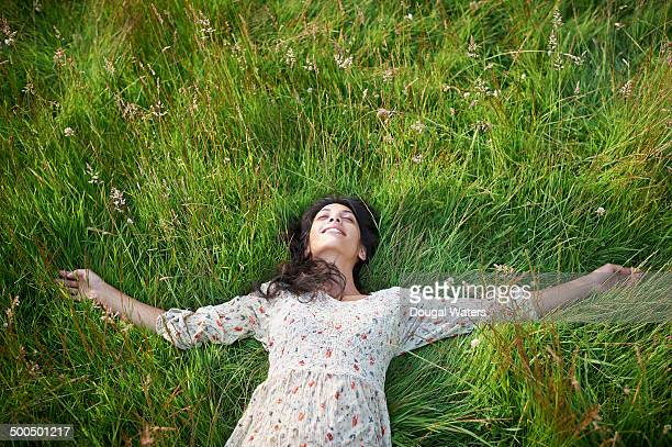 Woman laying in meadow with arms stretched