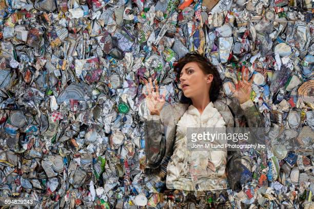 woman laying in pile of compacted trash - responsabilidad fotografías e imágenes de stock
