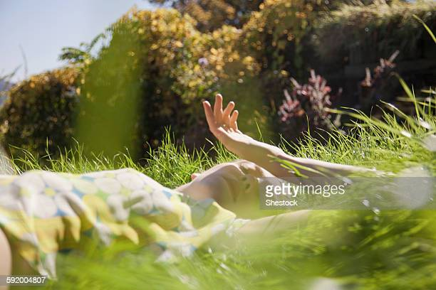 Woman laying in tall grass in park