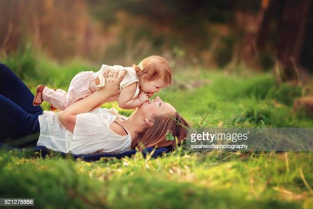 woman laying in the grass playing with her one year old daughter