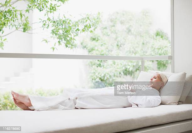 woman laying in window - erker stockfoto's en -beelden