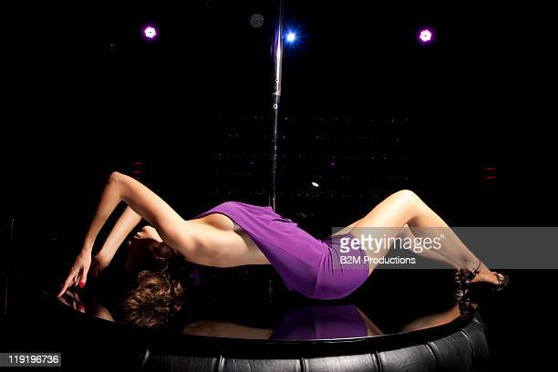 Woman laying near pole in club