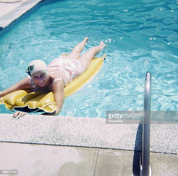 Woman laying on an air mattress in pool