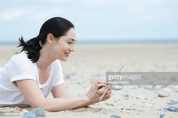 woman laying on beach using digital tablet. - newtechnology stock pictures, royalty-free photos & images