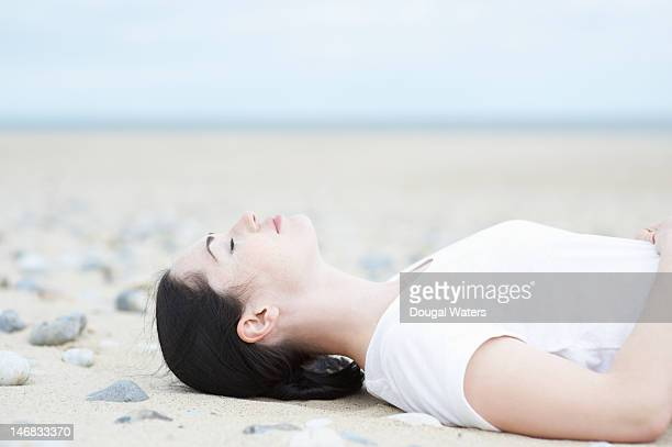 Woman laying on beach with eyes closed.