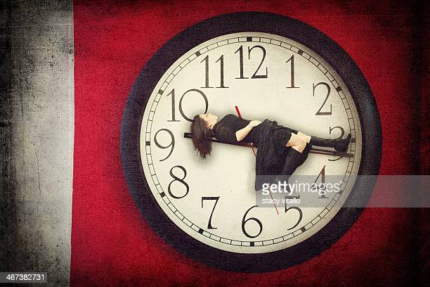 Woman laying on clock hands