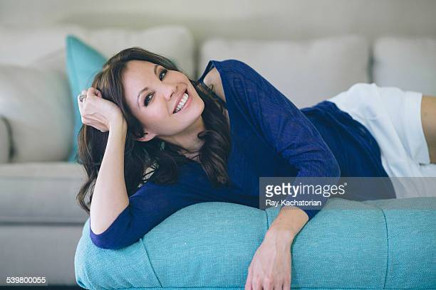 woman laying on couch smiling - one mature woman only stock pictures, royalty-free photos & images