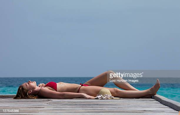 Woman laying on deck overlooking sea