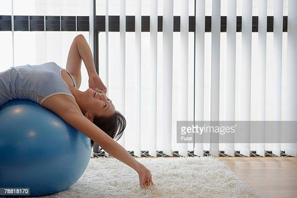 Woman Laying on Exercise Ball Using Cell Phone