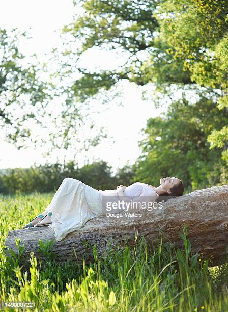 Woman laying on fallen tree trunk in countryside.