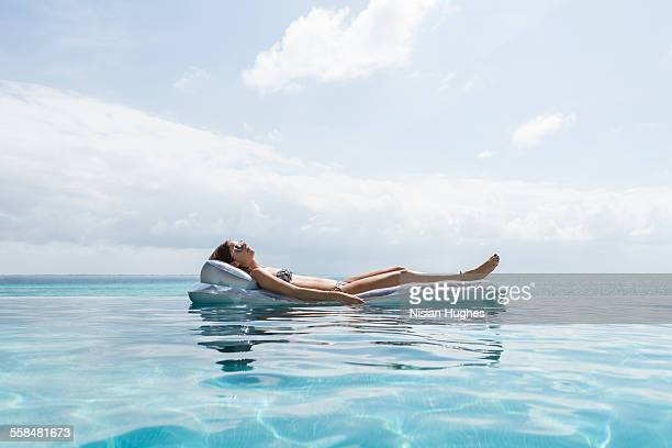 Woman laying on float mat in infinity pool