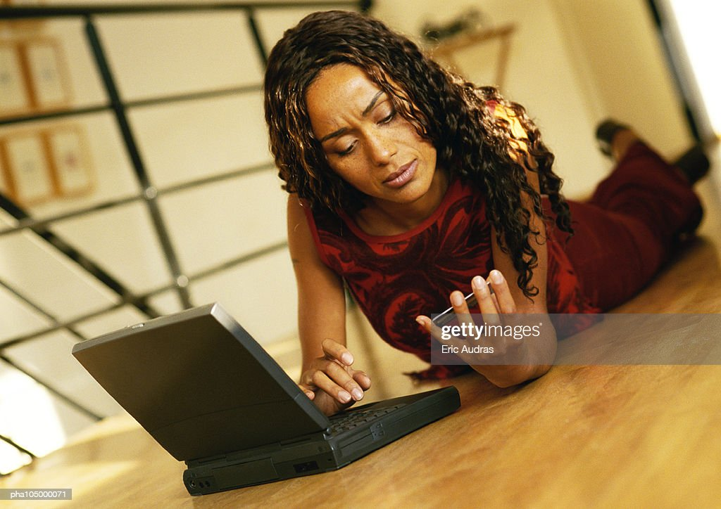 Woman laying on floor with laptop computer : Stockfoto