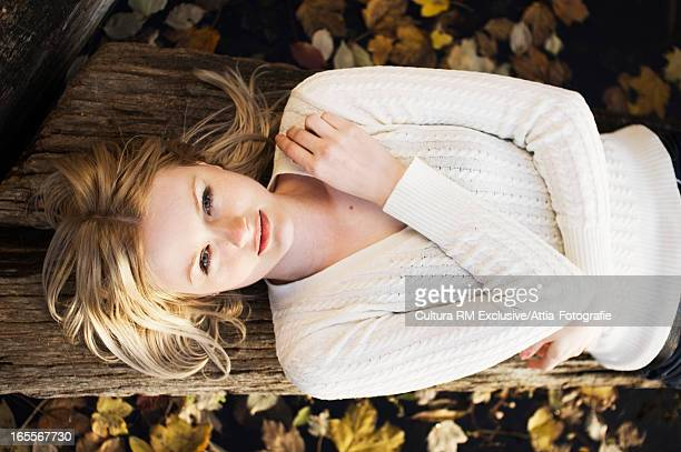 Woman laying on log in autumn leaves