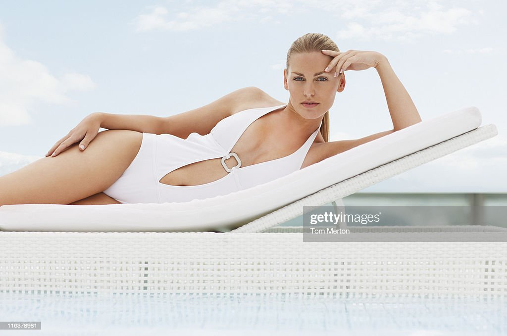 Woman laying on lounge chair at poolside : Stock Photo