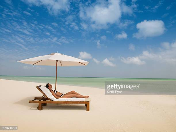 woman laying on lounge chair under beach umbrella - cadeira recostável - fotografias e filmes do acervo