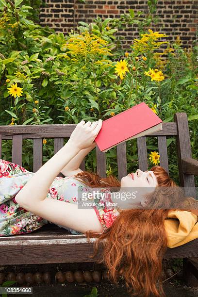 Woman laying on parkbench,reading book