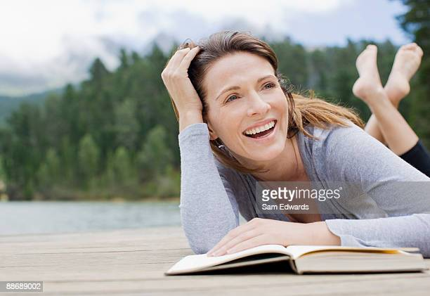 Colocación de lectura de mujer en el muelle