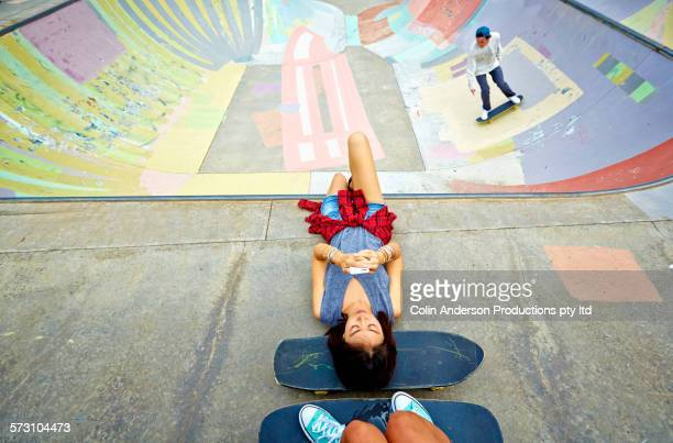 Woman laying on skateboard at skate park