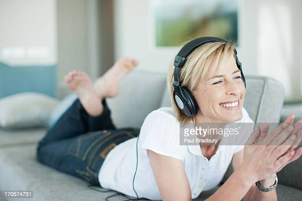 woman laying on sofa listening to headphones - one mature woman only stock pictures, royalty-free photos & images