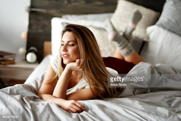 woman laying on stomach on bed. debica, poland - lazy poland stock photos and pictures