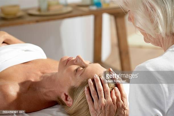 花輪を持つ女性のテーブルの頭部マッサージ