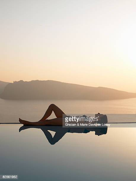 Woman laying on the edge of a pool