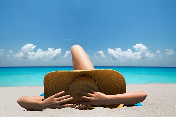 Woman laying on towel on beach